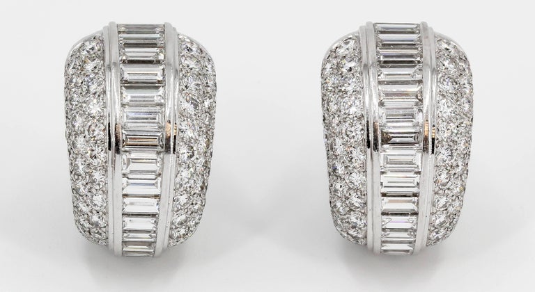 Very fine diamond and 18K white gold hoop earrings by Cartier. They feature high grade round and tapered baguette cut diamonds of F-G color and VVs clarity, approx. 10 carats total weight.  Hallmarks: Cartier, 750, reference numbers, maker's mark,