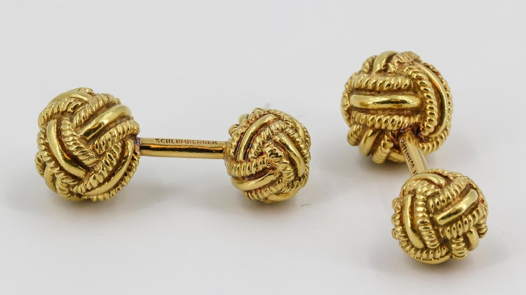 Timeless 18K yellow gold dumbbell cufflinks by Tiffany & Co., Schlumberger, circa 1970s. They feature a twisted rope knot design.  Hallmarks: Tiffany & CO., Schlumberger, 18k