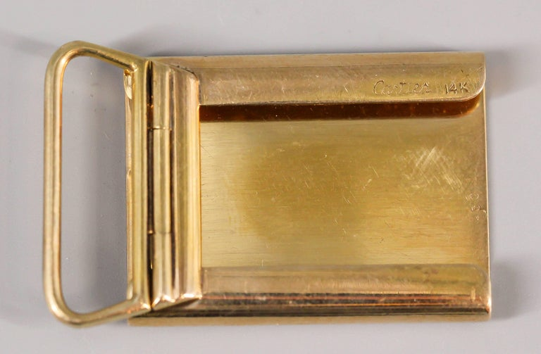 Whimsical 14K yellow gold belt buckle by Cartier, circa 1950s. It features an engine turned pattern front.  Handsomely made and highly usable.   Hallmarks: Cartier, 14k, reference numbers.