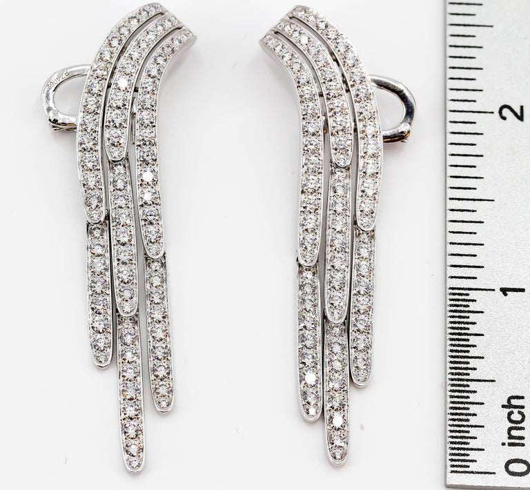 Chic diamond and platinum drop earrings by Cartier. They feature very high grade round brilliant cut diamonds of approx. E-G color, VVs clarity, total diamond weight approx. 10 carats.  Hallmarks: Cartier, 750, reference numbers