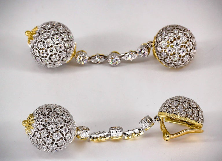 Stylish diamond and 18K yellow gold dangle earrings by Mario Buccellati, circa 1950s-60s. They feature high grade round brilliant cut diamonds throughout, and are in the shape of two spheres held together by a thin string of diamonds set in 18K