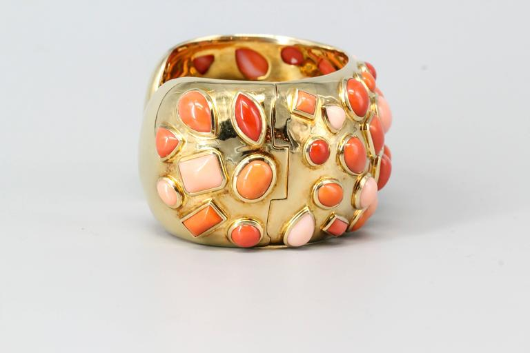 """Vibrant coral and 18K yellow gold cuff bracelet from the """"Fifties"""" collection, by Seaman Schepps. It features various geometric shaped inserts with different shades of coral pieces, from lighter to darker. Highly ornate and intricate with"""