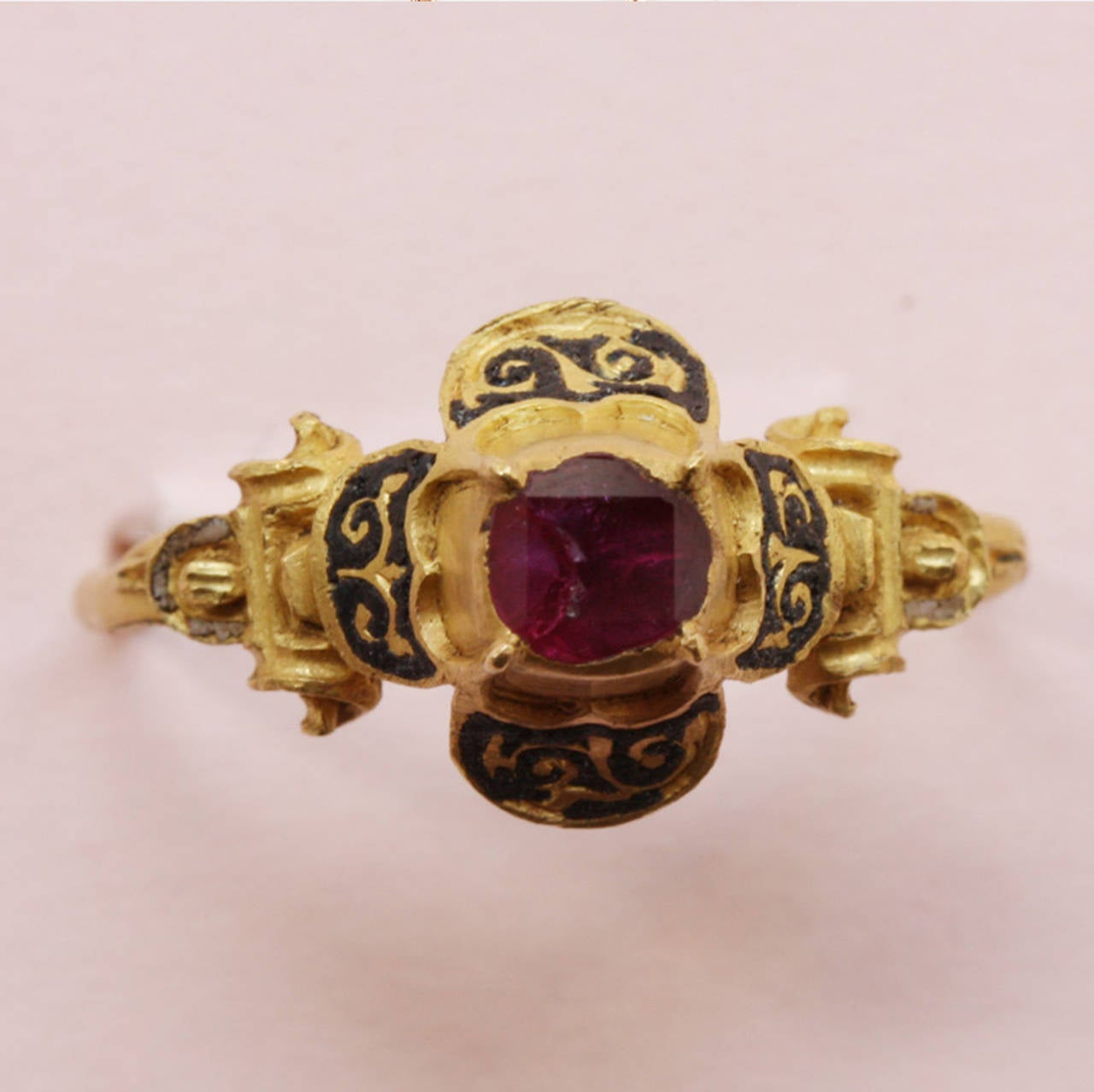 A high carat gold quatrefoil ring, the hoop merging with shoulders chased with volutes, with traces of white enamel, supporting a high quatrefoil bezel set with a table cut ruby, large black enamelled petals with foliate gold ornaments, 16th