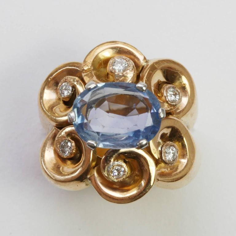 A pretty 18 carat gold ring set with a light blue oval cut Ceylon sapphire set with 6 white gold claws, surrounded by 6 gold waves each wave decorated with a small old cut diamond (app. 0.04 carat, in total 0.24 carats), France, circa 1940.  ring