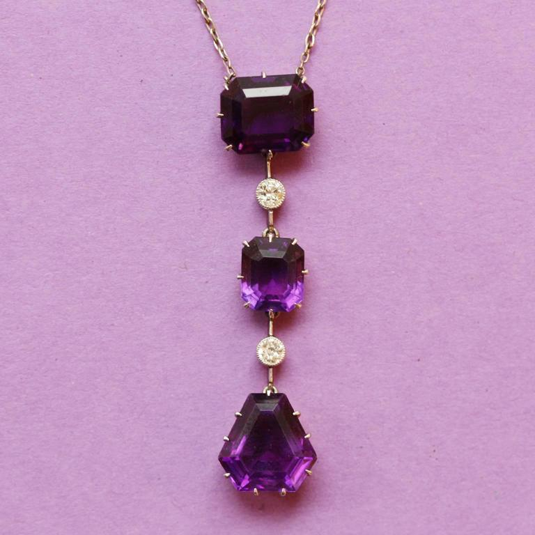 Amethyst and diamond pendant. Horizontally set to top and vertically set to centre with emerald-cut natural unenhanced amethysts of the most perfect deep purple color, with one further to the lower drop in a kite shape step cut form (app. 8.00