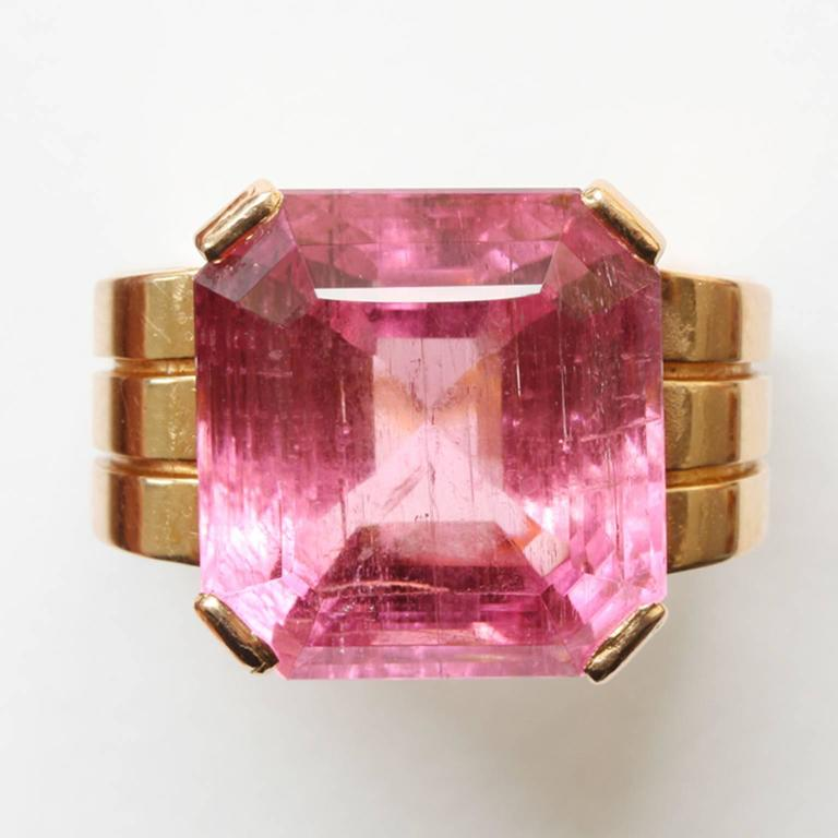 A large 18 carat rosé gold tank ring set with a square step cut bright pink tourmaline (app. 20 carats), masters mark: Henry Fougery and fully signed: Mathy, Paris for Charles Mathy, France. circa 1925-1930.  weight: 21.4 grams ring size: 18