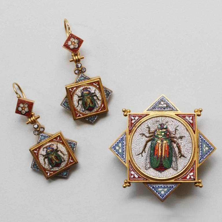 An 18 carat gold micromosaic Egyptian Revival suite consisting of a brooch and a pair of earrings, the micromosaics are decorated with beetles with little gold accented 'tesserae' the gold has applied wirework and beads and Papal marks for Italy