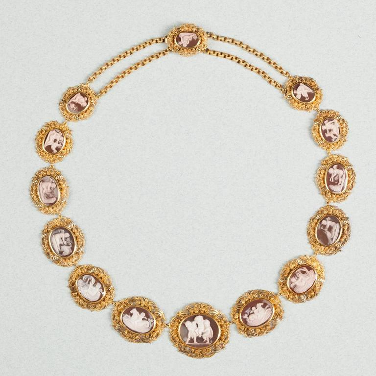 A 15-carat gold necklace set with 14 sardonyx cameos with genre scenes of Amor, the god of love, set in a rich Georgian mount with fine spirals (cannetille) and granules (grainti), a double textured chain links the last cameos to the clasp,