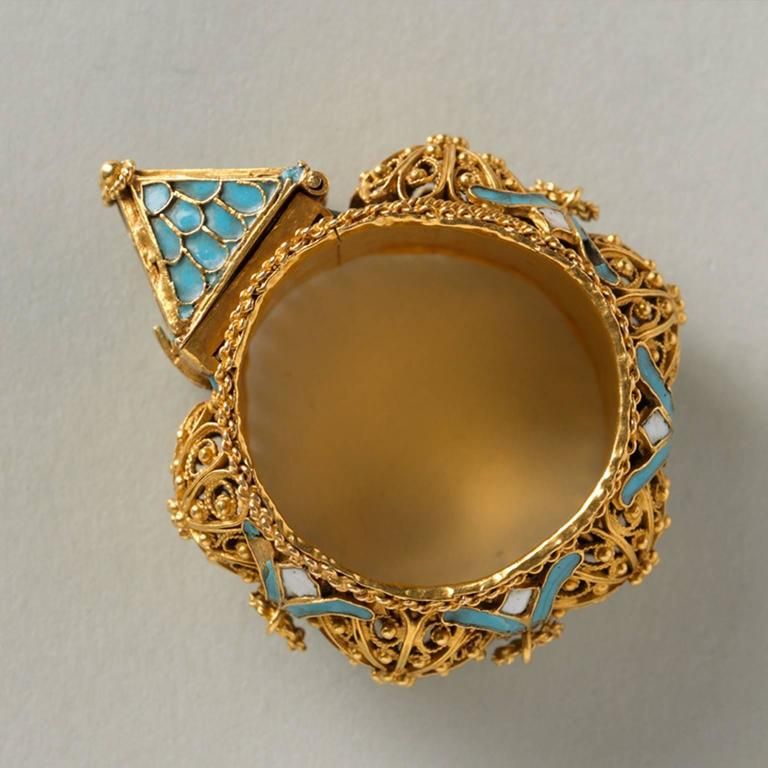 An important Jewish-marriage ring; hoop large and broad gold band, with filigree bosses enriched with little flowers in between, on which are loops of twisted gold wire (one is missing); twisted wires along the edges and white and blue enamel; on
