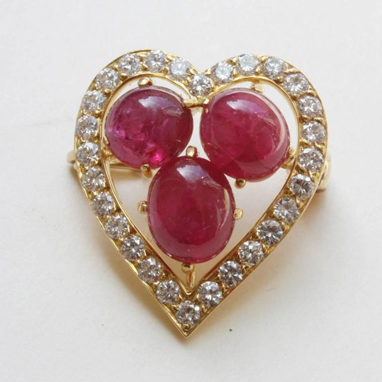 A sweet little 18 carat gold brooch in the shape of a heart, set with 28 brilliant cut diamonds (app. 0.56 in total, VS2, G-H) in the center three cabochon cut natural rubies (7 x 6 mm), signed and numbered: Cartier, Q4269.  weight: 4.3