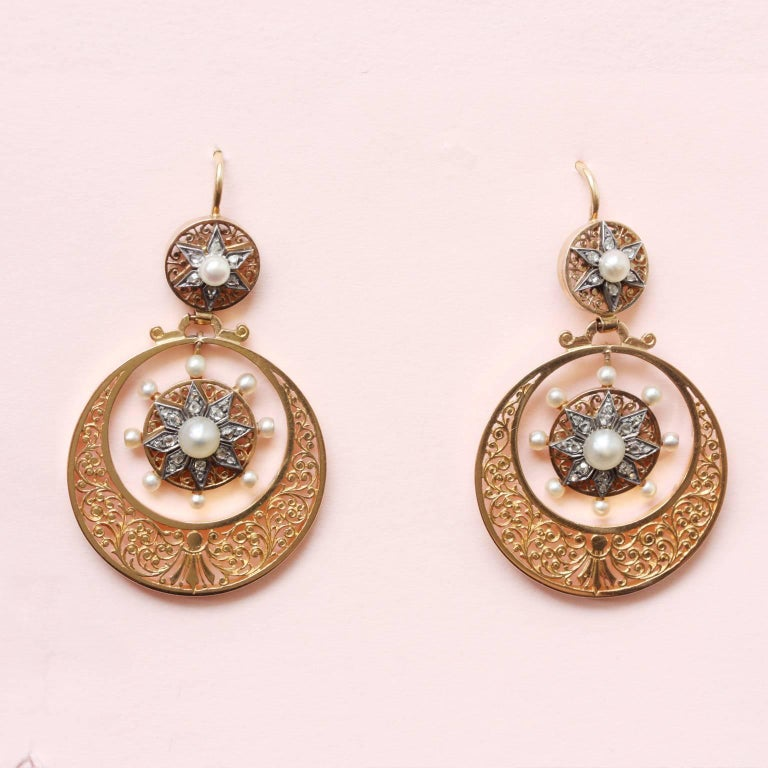 A pair of 18 carat gold circle earrings with a hand engraved foliage decoration, inside a drop with silver stars set with rose cut diamonds  and pearls, with similar tops, France, Savoy, 19th century.  weight: 12 grams length: 4.5 cm