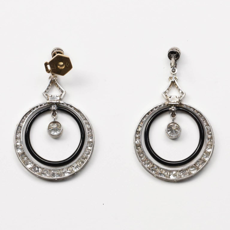 A pair of platinum and diamond (app. 3.6 carats) Art Deco earrings set with old-cut diamonds, the top is a small cabochon-cut onyx below which are two hoops connected by a triangle: the inner hoop is decorated with black enamel and the outer hoop is