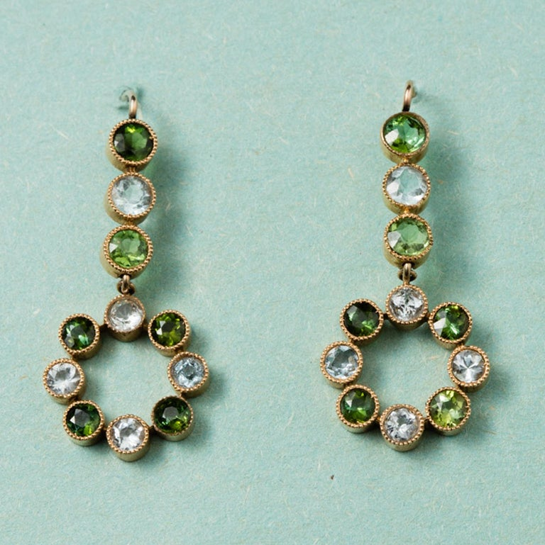 A pair of 15 carat gold earrings with a circle where round aquamarines alternate green tourmalines, circa 1910, England.  weight: 5.7 grams dimensions: 3.7 x 1.5 cm