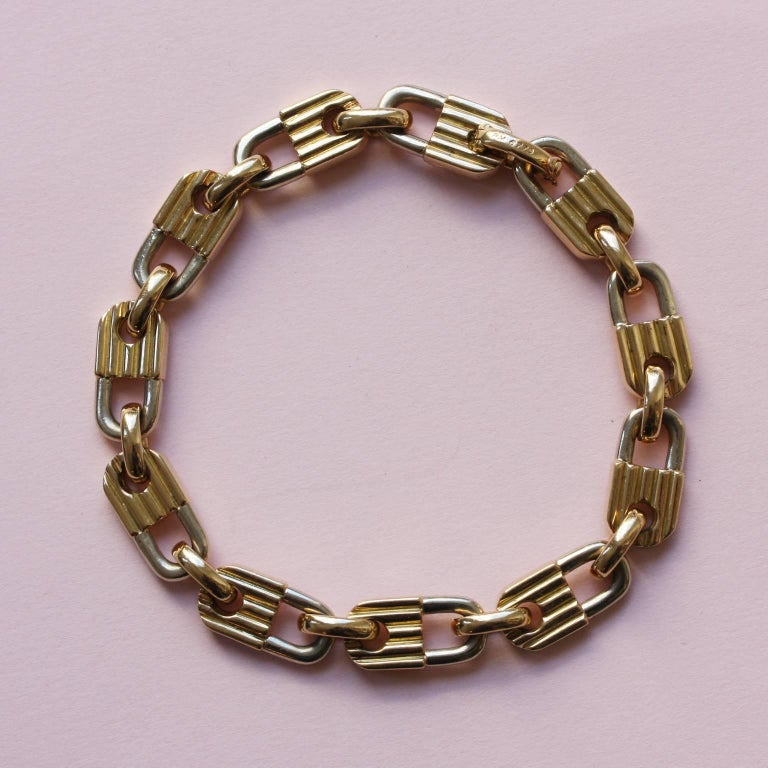 A bi-color 18 carat gold bracelet consisting of 11 links in the shapres of locks, the brackets are white gold and the locks are yellow gold and ribbed, in between are yellow gold oval links, signed and numbered: Mauboussin, Paris, PM 6779.  length: