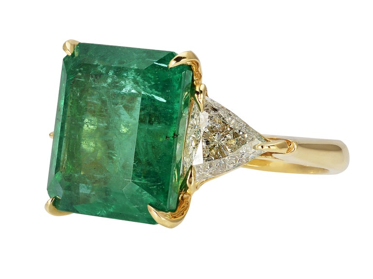 18 Karat Yellow Gold Three Stone Cocktail Ring Featuring A 10 Carat Emerald GIA Graded As Zambian In Origin. Two Trilliant Cut Side Diamonds Total 1.40 Carats Of I1 Clarity & H Color. Hidden Hearts in Gallery. Finger Size 6; Purchase Includes Free