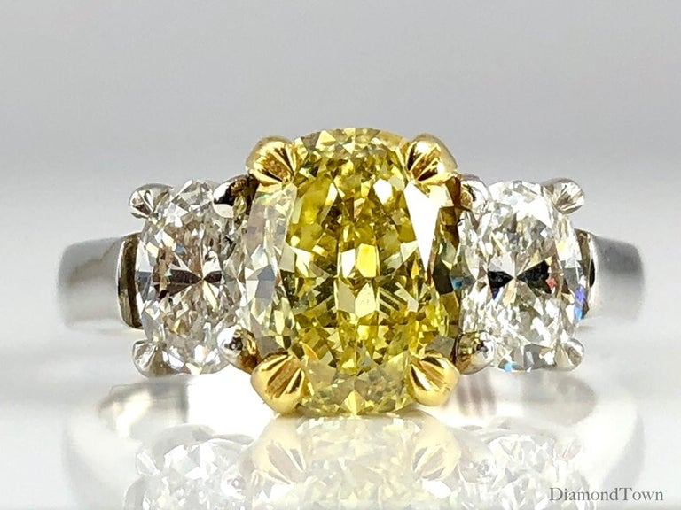 This gorgeous ring features a GIA Certified 2.01 Carat Natural Fancy Intense Yellow Oval Cut diamond center, flanked by two large oval cut round white diamonds. The total diamond weight is 2.88 carats.  Ring size 6, with room to size up or down. Set