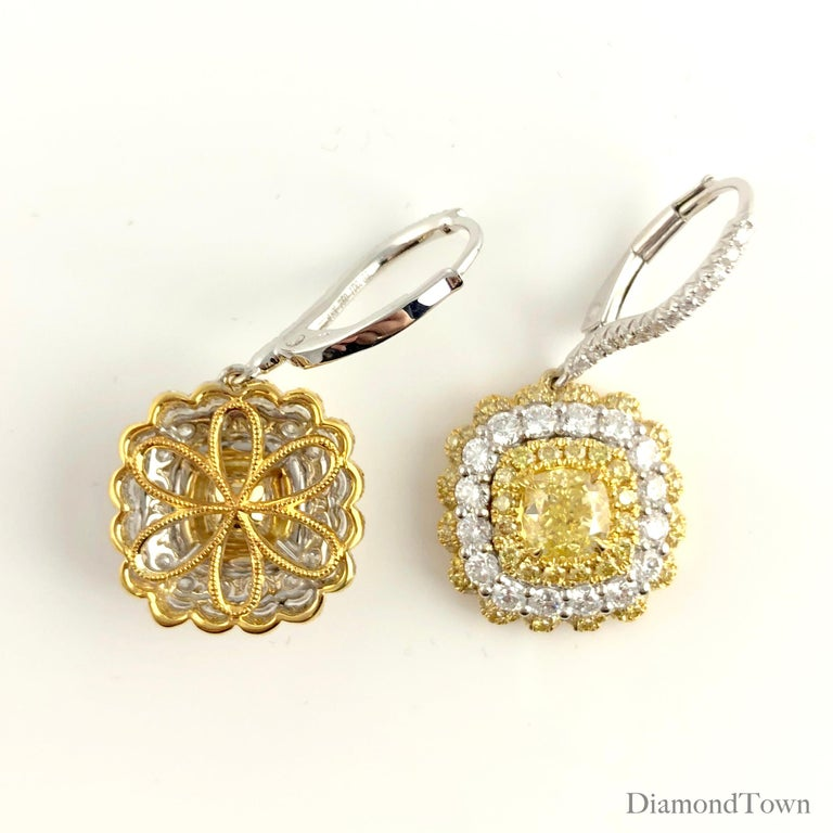 These earrings feature GIA certified Natural Fancy Yellow cushion cut centers, each surrounded alternating halos of round yellow and round white diamonds. The certified centers measure 1.30 carats total, however the halos bring the earrings' total