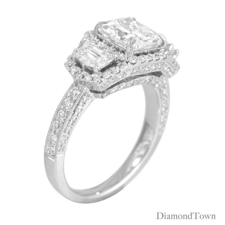 This stunning handcrafted ring features a 1.72 carat GIA certified cushion cut center, flanked by two half-moon diamonds. Each of the main three stones is surrounded by a halo of round white diamonds, which also continues down the side shank and