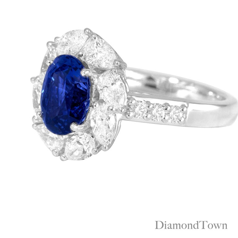 This ring features a 2.54 Carat Oval Cut Vivid Blue Ceylon Sapphire center, surrounded by a halo of eight Pear Shape diamonds. Additional diamonds trace down the side shank, bringing the total diamond weight to 1.42 carats. An intricate under
