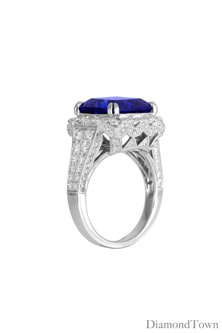 This ring features a 6.99 carat Vivid Blue Tanzanite cushion cut center surrounded by a halo of diamonds. Intricate milgrain work and trails of round diamonds extending down the shank make this ring shine from all angles. Total diamond weight 1.62