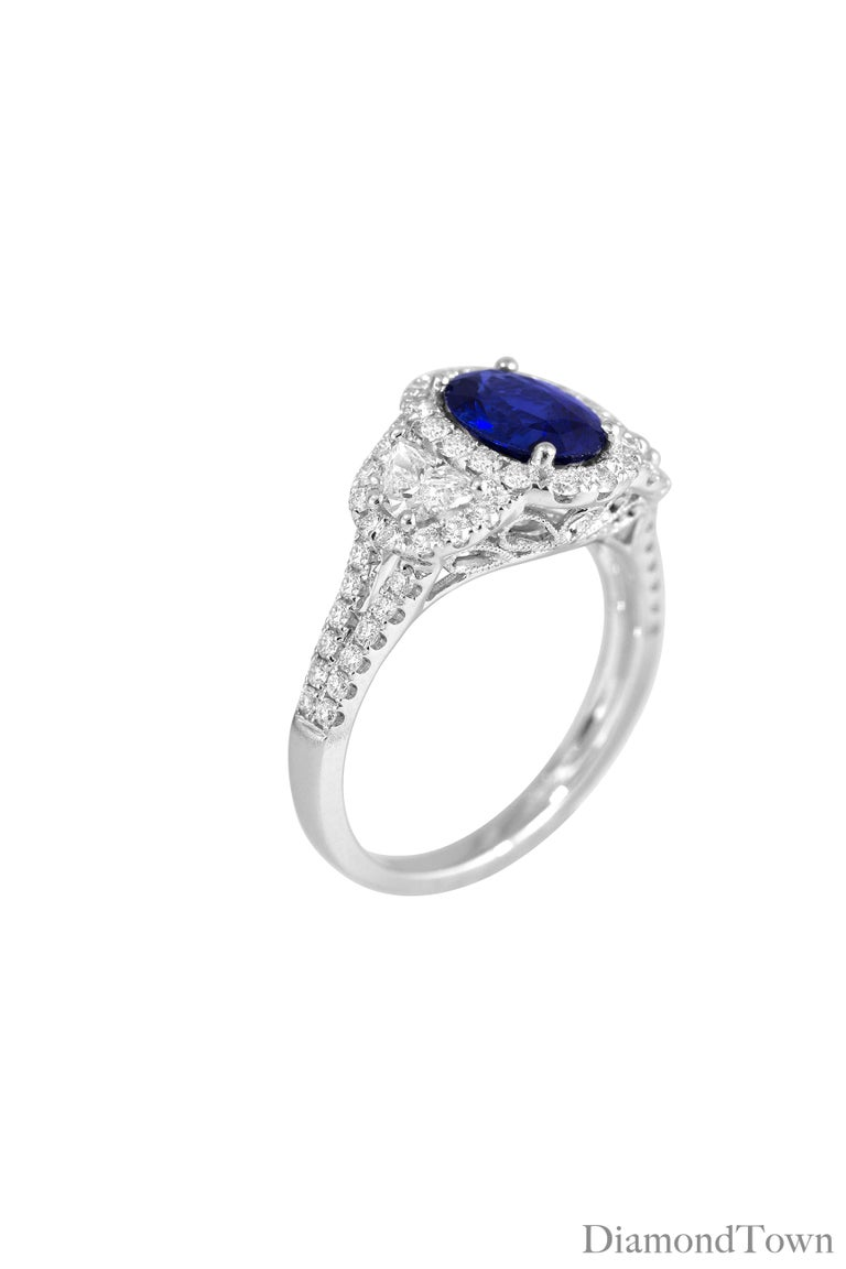This ring features a 2.26 Carat Oval Cut Vivid Blue Ceylon Sapphire center, surrounded by a halo of white diamonds, and flanked by two half-moon diamonds, with their own additional halo of diamonds. Round diamonds extending down the side shank, fine