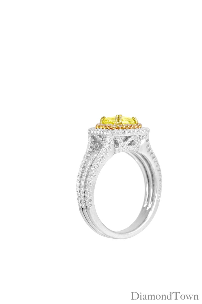 This beautiful ring features a 1.00 carat GIA-certified Natural Fancy Yellow diamond Cushion cut center surrounded by two halos of pink diamonds and white diamonds, bringing the total diamond weight to 1.79 carats. An intricate diamond under gallery