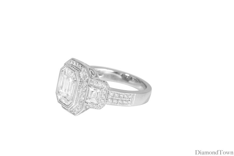 This ring features a center cluster of baguettes around 1 emerald cut diamond. An additional halo of round diamonds, and diamonds down the shank bring the total diamond weight to 1.66 carats. Intricate milgrain work.  Set in 18k White Gold Ring size