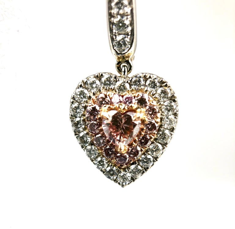 Show your love with these beautiful earrings, which feature 0.32 carat pink heart shaped diamonds, surrounded by halos of pink and white diamonds. Additional diamonds in the decorated under gallery make these earrings beautiful from all angles.