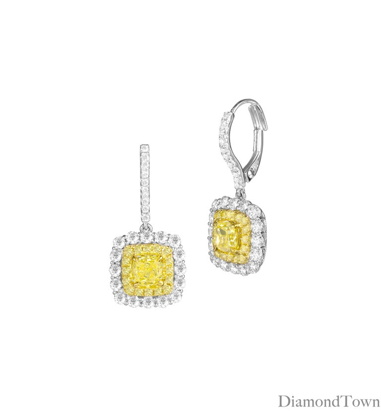 These stunning earrings feature GIA Certified Natural Fancy Intense Yellow cushion cut diamond centers, surrounded by halos of yellow and white diamonds, bringing the total diamond weight to 3.32 carats. Intricate milgrain work in the yellow gold