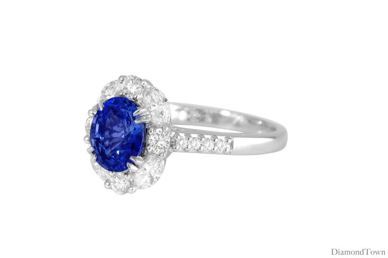 This ring features a GAL certified 1.83 carat Oval cut Ceylon Sapphire surrounded by a halo of round white diamonds, and additional diamonds down the side shank (total diamond weight 0.78 carat).  The ring is set in 18k White Gold. Ring size 6.5,