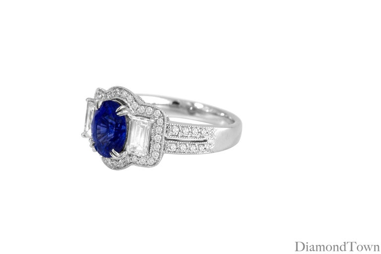 This ring features a 1.44 carat GAL Certified Oval Cut Blue Sapphire center, flanked by 2 baguette diamonds and encircled by additional round diamonds. Total diamond weight 0.87 carats. Intricate milgrain work and a beautiful under gallery complete