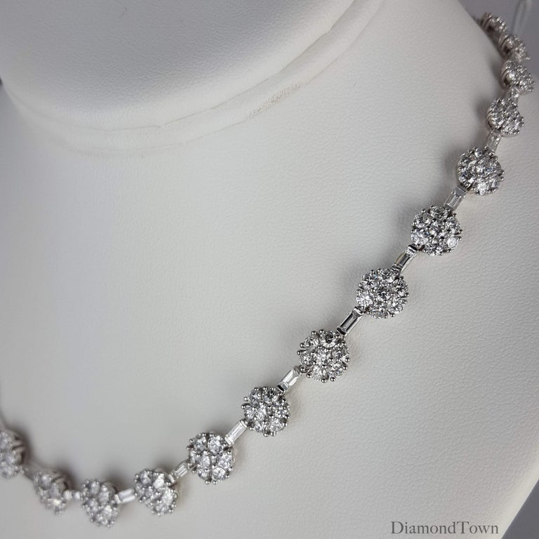 This stunning necklace features 32 diamond flowers in a graduated pattern, linked by baguette diamonds. Each flower is made of 8 beautiful round diamonds. Total diamond weight 21.84 carats, set in 18k White Gold.  Necklace measures 17