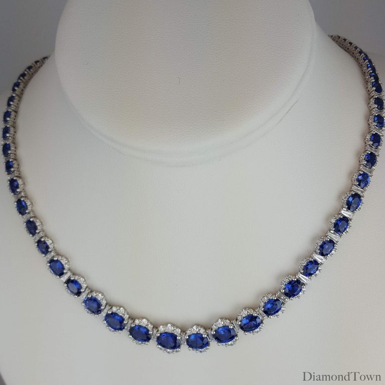 This necklace features graduated oval cut Vivid Blue Sapphires (total weight 34.03 carats) alternating with tapered baguette diamonds and surrounded by additional round cut diamonds (total diamond weight 6.89 carats). The Sapphire and Diamond