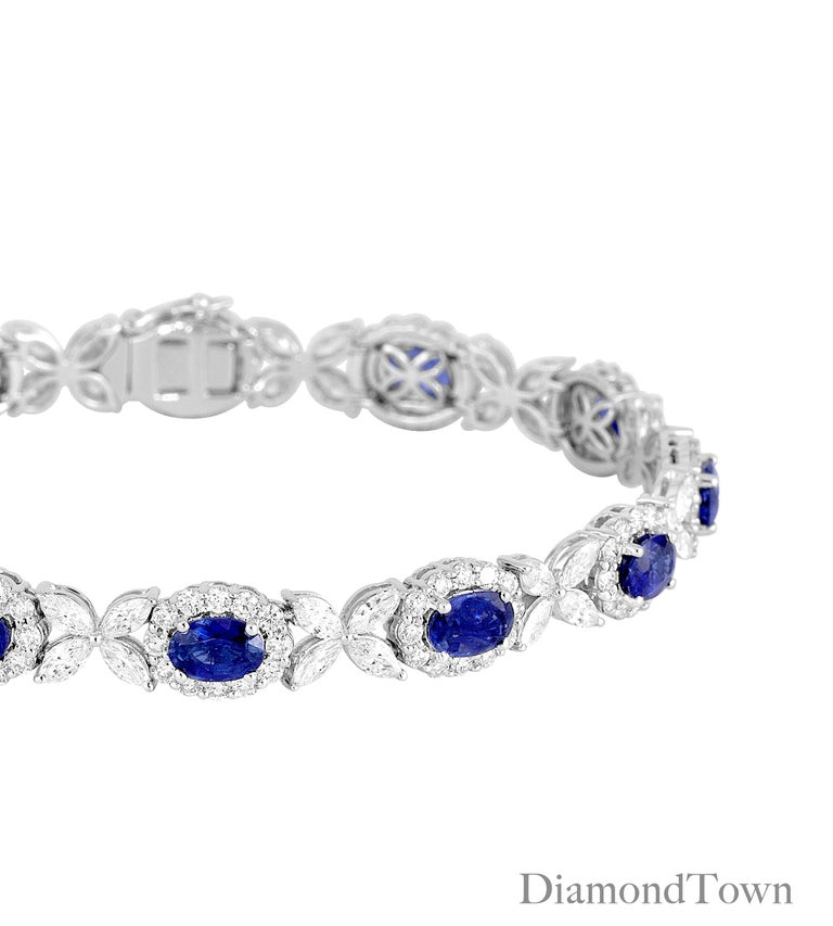 This bracelet features 11 Oval Cut Vivid Blue Sapphires (total weight 8.14 carats), each in a halo of round diamonds, and alternating with flowers of marquise cut diamonds. The total diamond weight is 6.95 carats.  Bracelet measures 7