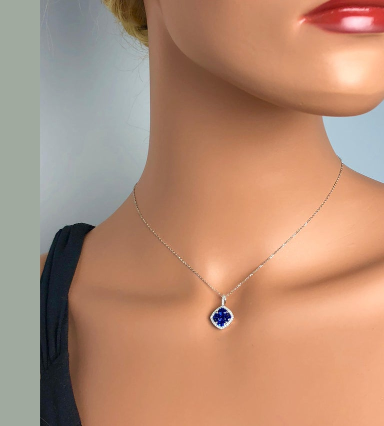 This pendant features a rounded square cluster of four oval cut and one princess cut vivid blue sapphires (total weight 1.09 carats), surrounded by a halo of round white diamonds, which also extend up the bail (total diamond weight 0.13