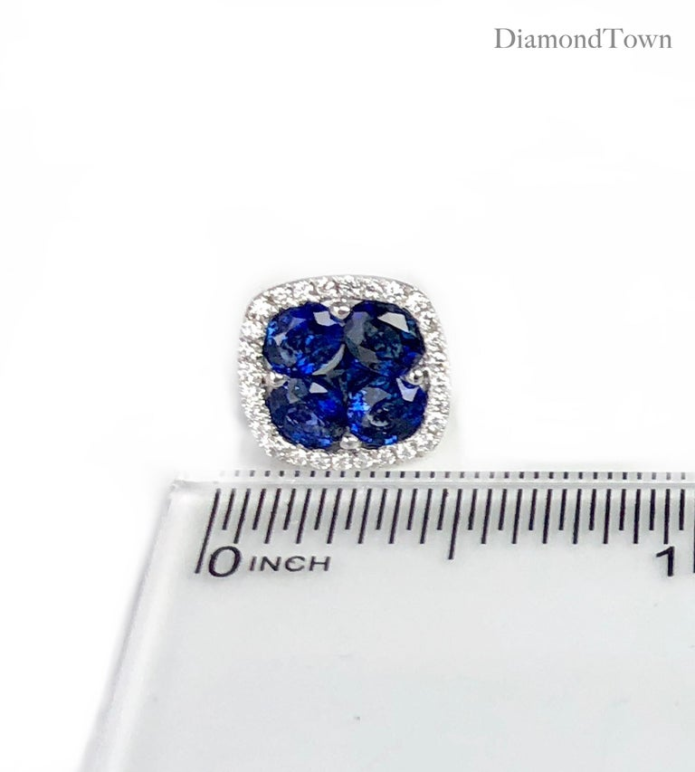 These stud earrings feature a cluster center of blue sapphires (five stones per earring, total weight 2.65 carats) surrounded by a halo of round white diamonds (total diamond weight 0.26 carats), set in 18k white gold.  There is a seasonal promotion