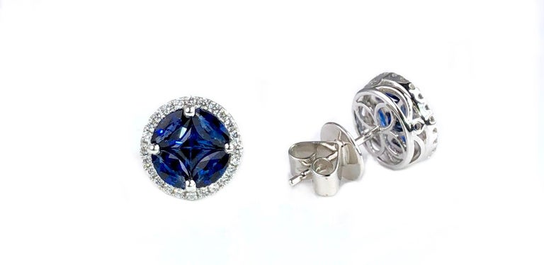 These round stud earrings feature a cluster center of blue sapphires (total weight 1.72 carats), surrounded by a halo of round white diamonds (total weight 0.21 carats).  Set in 18k White Gold  There is a seasonal promotion available on this piece.
