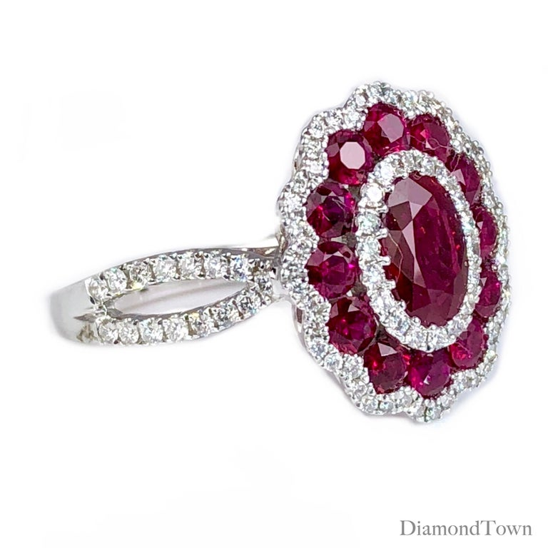 This beautiful ring features one oval cut Ruby center, surrounded by alternating halos of round white diamonds and round rubies. Additional round diamonds down the split shank complete the look (total diamond weight 0.44 carats).  Set in 18k White