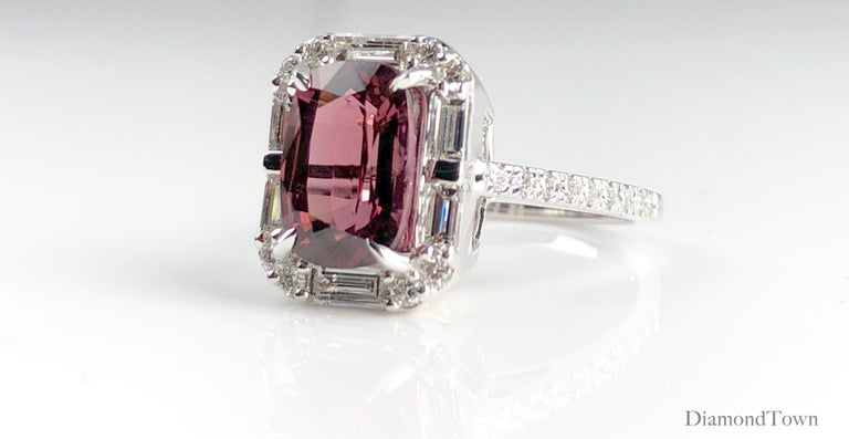This beautiful ring features a 4.95 carat cushion cut Raspberry Garnet center, surrounded by a halo of baguette  and round diamonds. Additional round diamonds trace down the side shank, bringing the total diamond weight to 1.19 carats.  Ring size