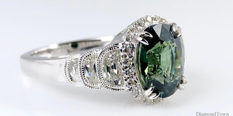 This gorgeous ring features a 2.86 carat oval cut Forest Green Sapphire center, surrounded by a halo of round white diamonds. Each side shank features 3 half moon diamonds of descending size, decorated with detailed milgrain work.  Ring size 6.5,