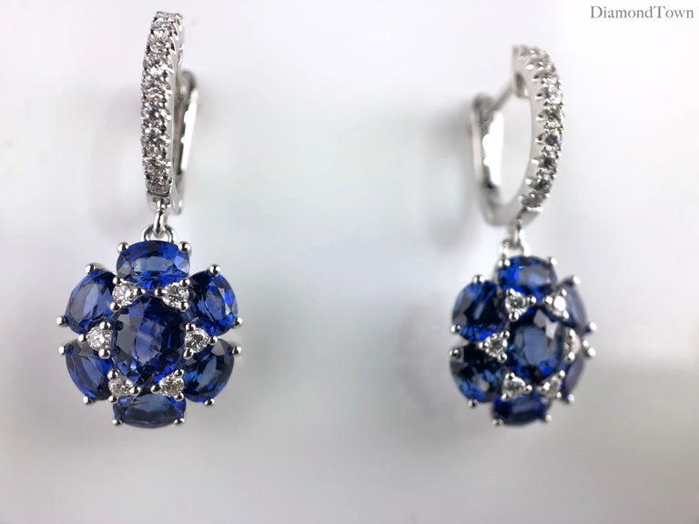 These sparkling dangle earrings feature flowers made of 7 oval cut blue sapphires arranged among 6 round diamonds (total diamond weight 0.32 carats).  Set in 18k White Gold.  There is a seasonal promotion available on this piece.  For details please