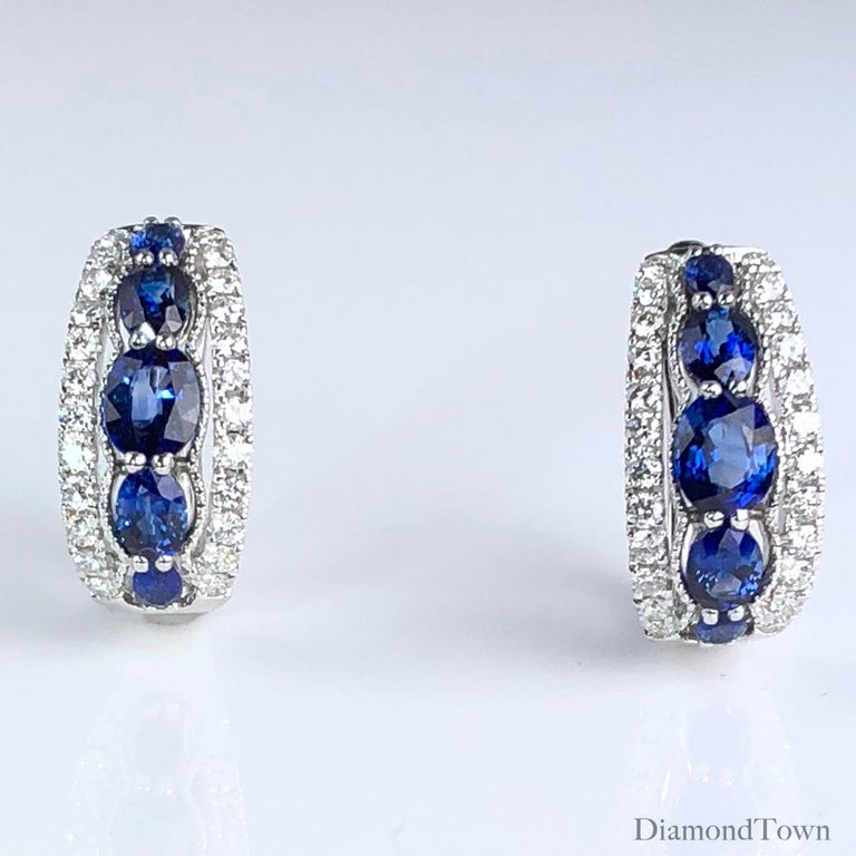 These earrings feature 5 graduated oval cut sapphires each (total weight 2 earrings 1.94 carats), wrapped on both sides with white diamonds (total diamond weight 0.54 carats). The earrings close securely by lever-back, and are set in 18k white