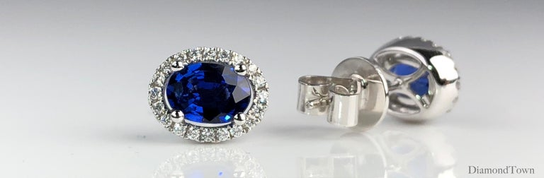 These lovely earrings feature an oval cut vivid blue sapphire (total weight 1.65 carats), surrounded by a a halo of round white diamonds (total weight 0.19 carats).  Many of our items have matching companion pieces. Please inquire.