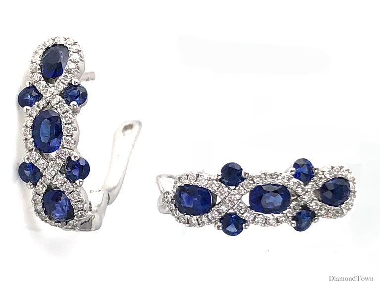 These stunning earrings feature round and oval cut vivid blue sapphires (total carat weight 2.52 carats) in an interlaced design of round white diamonds (total diamond weight 0.48 carats).  Set in 18k White Gold. Lever-back closure.  There is a