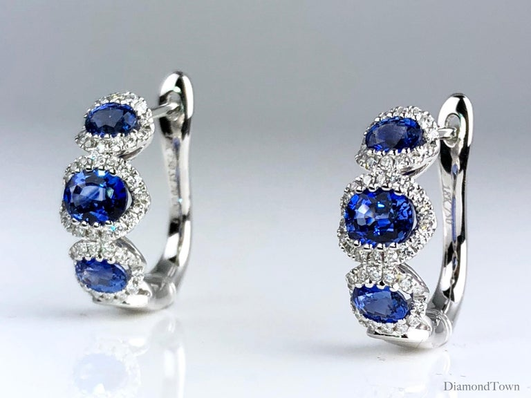 These gorgeous Diamond Town earrings feature three vivid blue oval cut sapphires, each inside a halo of round white diamonds. The earrings close securely by lever-back and are set in 18k White Gold.  Many of our items have matching companion pieces.