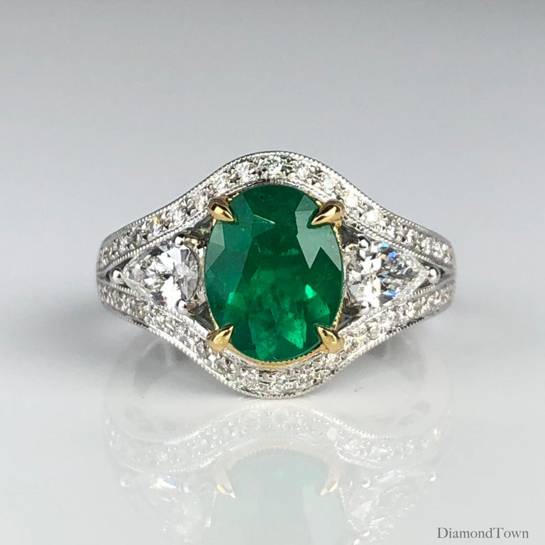 This sparkling ring features a 1.70 carat oval cut fine emerald center, flanked by pear shape diamonds and surrounded by a halo of round diamonds.extending down a split shank.  The center is set in a yellow gold accent, highlighted against the rest