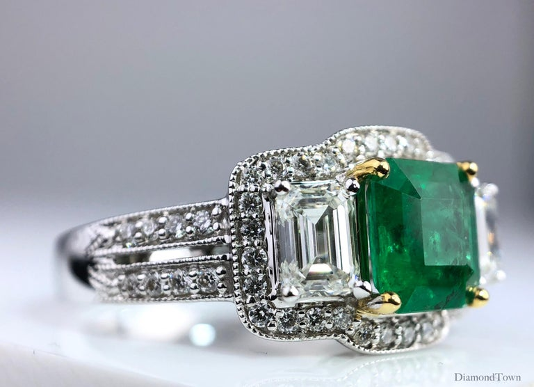 This gorgeous ring carries a 1.10 carat cushion cut Colombian Emerald center, flanked by baguette diamonds and surrounded by round white diamonds. Additional round diamonds trace down the split shank, bringing the total diamond weight to 1.03
