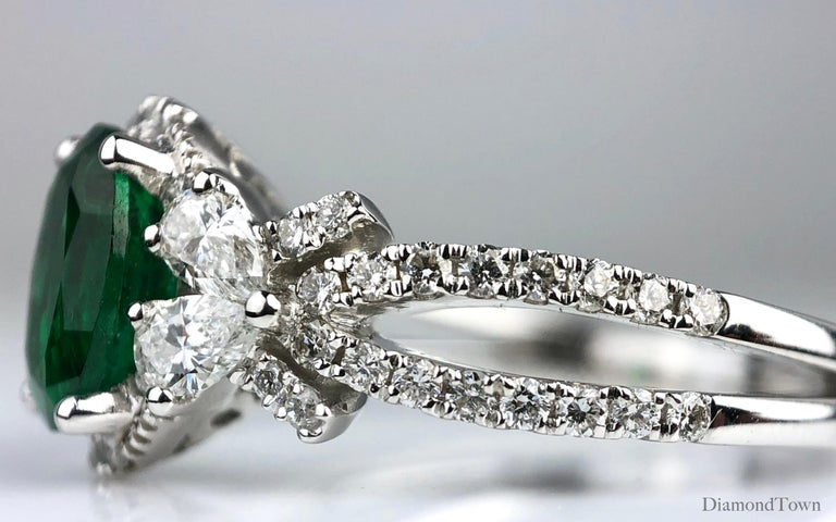 This ring features a deep green 1.21 carat oval cut fine emerald center, flanked by four pear shaped diamonds and additional round diamond halo, and round diamonds tracing down the split shank. From the side, the diamonds give the impression of a