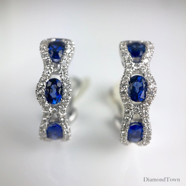 These lever-back stud earrings feature three oval cut vivid blue sapphires each, wrapped in a web of round white diamonds. Total sapphire weight is 1.23 carats. Total diamond weight 0.35 carats.  Set in 18k White Gold.  There is a seasonal promotion
