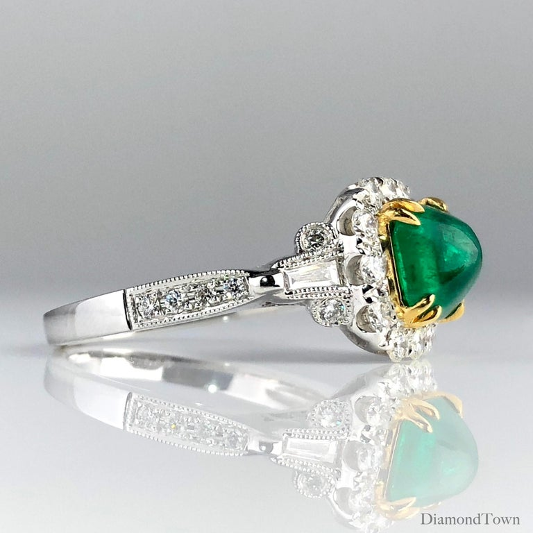 This ring features a 1.45 carat sugarloaf Colombian Emerald center, surrounded by a square halo of round white diamonds. Two tapered baguettes and additional round diamonds lead down the side shank, bringing the total diamond weight to 0.79